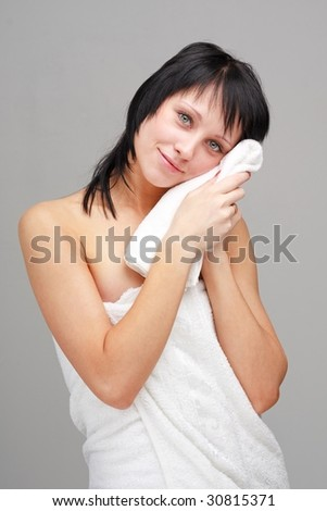 Attractive young woman with towel on a gray background.