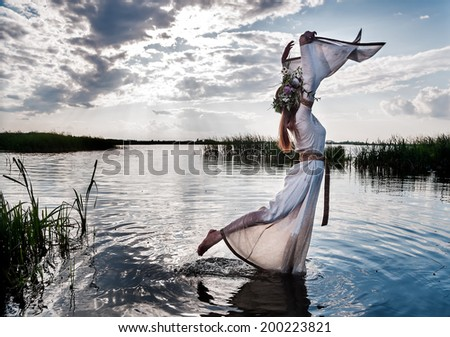 Attractive young woman with wreath of flowers walking in lake water. Russian traditional Ivan Kupala holiday celebration - stock photo