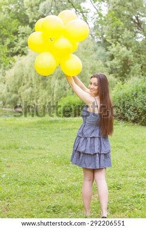 Attractive Young Woman with Yellow Balloons at Beautiful Summer Day Outdoor. Happy female enjoying nature. - stock photo