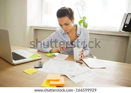 Attractive young woman working at the desk with sticky notes and laptop. Beautiful businesswoman reading notes while sitting in home office. - stock photo