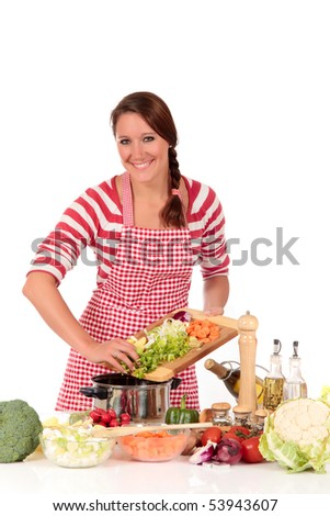 Attractive Young woman working in kitchen, preparing soup.  Bowls with vegetables in foreground.  Studio, white background. - stock photo