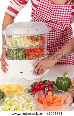 Attractive Young woman working in kitchen, preparing steamed vegetables in steam cooker.  Studio, white background.