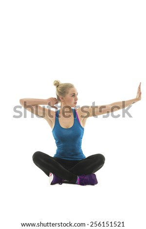 Attractive young woman working out doing yoga stretching exercises with her arms as she sits cross legged in the lotus position on the floor, over white - stock photo