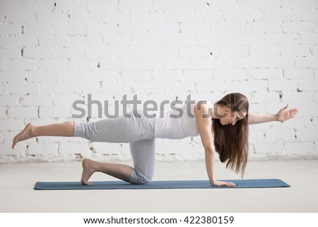 Attractive young woman working out indoors. Beautiful model doing exercises on blue mat in room with white walls. Bird-dog or kneeling opposite arm and leg extension (chakravakasana). Full length - stock photo