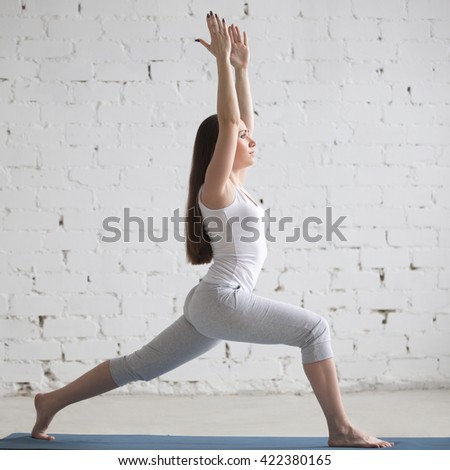 Attractive young woman working out indoors. Beautiful model doing exercises on blue mat in room with white walls. Warrior 1 or Virabhadrasana I pose. Square image. Full length - stock photo