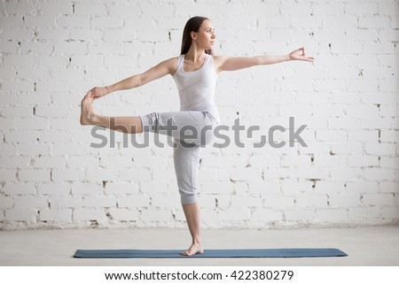 Attractive young woman working out indoors. Beautiful model doing exercises on blue mat in room with white walls. Parivrtta Utthita Hasta Padangustasana, Revolved Extended Hand to Big Toe. Full length - stock photo