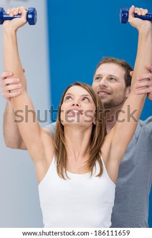 Attractive young woman working out with a personal trainer at a gym lifting a pair of dumbbells above her head as he supports her arms form behind - stock photo