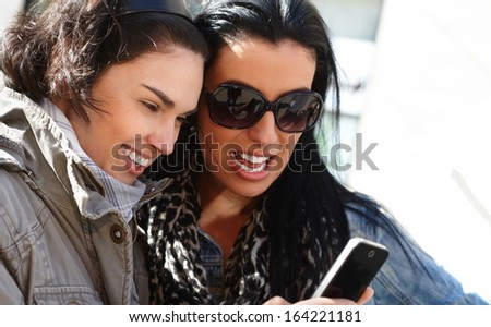 Attractive young women looking at smartphone, laughing at picture or text message. - stock photo
