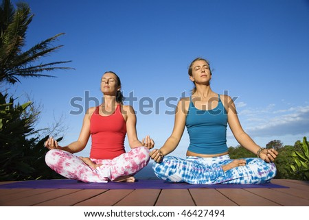 Attractive young women sit in the yoga lotus position on a deck and yoga mat. Horizontal shot. - stock photo
