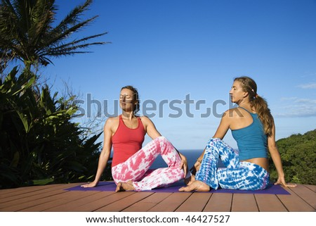 Attractive young women sit on an exercise mat doing yoga on a deck with the ocean in the background. Horizontal shot. - stock photo