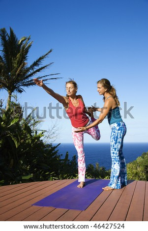 Attractive young women stand on an exercise mat doing yoga outdoors with the ocean in the background. Vertical shot. - stock photo
