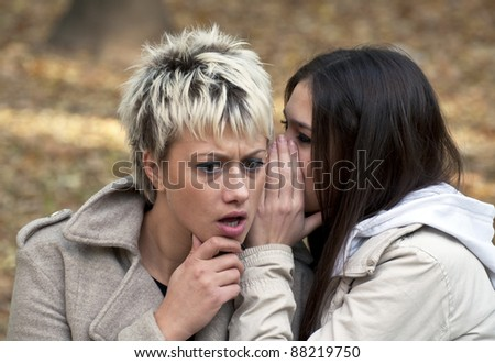 Attractive young women whispering secrets in park - stock photo