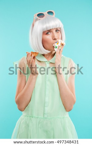 Attrative young woman standing and eating cupcake by hands