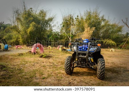 ATV, an all-terrain vehicle, also known as a quad, quad bike, three-wheeler, four-wheeler, or quadricycle, parking beside the race track - stock photo