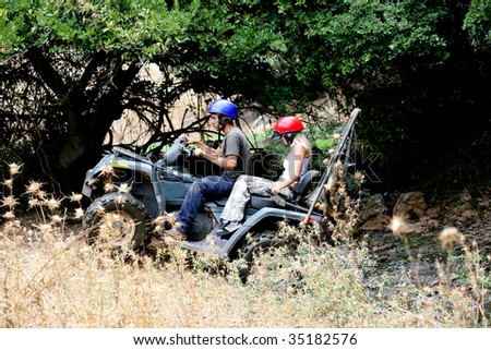 ATV climbing with lush green background - stock photo
