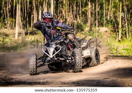 ATV racer takes a turn during a race on a dusty terrain. - stock photo
