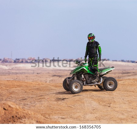ATV rider in the desert summer day - stock photo