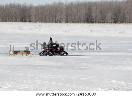 ATV with traction belt on frozen river