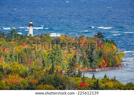 Au Sable Light Station, a lighthouse on the Lake Superior Coast of Michigan's Upper Peninsula, is surrounded by colorful autumn foliage. - stock photo
