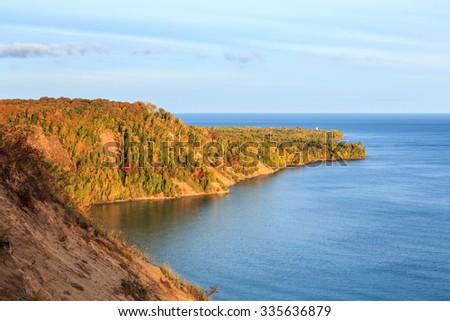 Au Sable Point in the upper peninsula of Michigan. Sunrise illuminates autumn foliage surrounding the Lighthouse with Lake Superior in the background. - stock photo