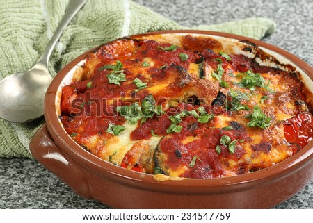 aubergine red peppers and mozzarella cheese baked in a terracotta dish                                - stock photo