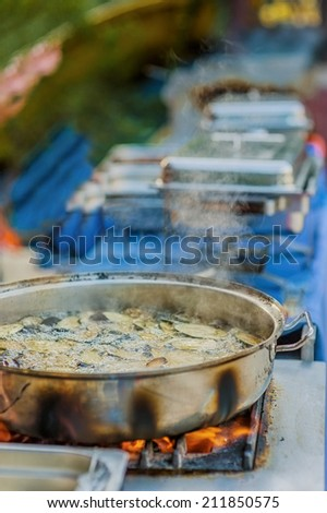 Aubergine with oil boil on frying pan. - stock photo