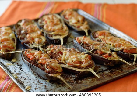 Aubergines baked with minced meat and cheese on a baking sheet.