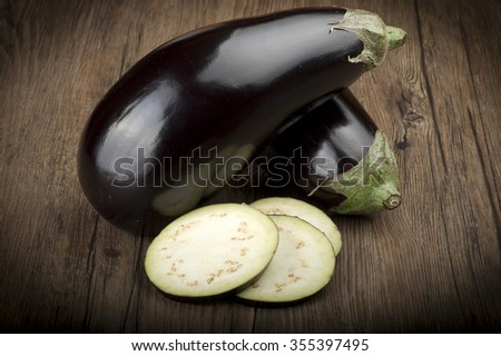 Aubergines eggplants and slices on wood background - stock photo