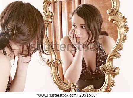 auburn-haired girl, young woman in front of a mirror - stock photo