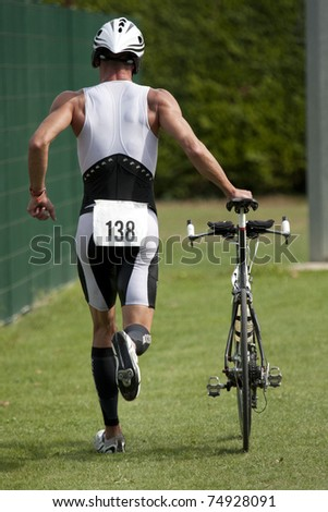 """AUCH, FRANCE - SEPTEMBER 4:  An unidentified male competitor runs though the transition area of the """"Auch triathlon"""" on September 4, 2010, in Auch, France. - stock photo"""
