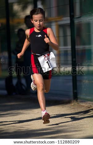 AUCH, FRANCE - SEPTEMBER 8: an unidentified young female runner, Auch Triathlon, on September 8, 2012 in Auch, France. - stock photo