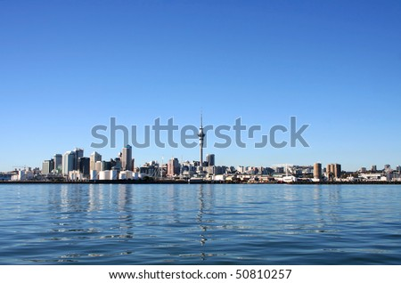 Auckland City and Sky Tower, New Zealand with bright blue clear skies viewed from across the harbour - stock photo
