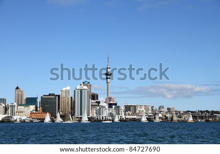 Auckland City and Skytower with yachts sailing past on a clear sunny day.  Viewed from across the Waitemata Harbour, Auckland, New Zealand - stock photo