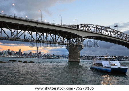 Auckland harbor bridge and ferry with Auckland city CBD at sunset in Auckland, New Zealand. - stock photo