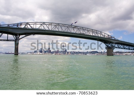 Auckland Harbour Bridge with Auckland City and Sky tower in the background, New Zealand - stock photo