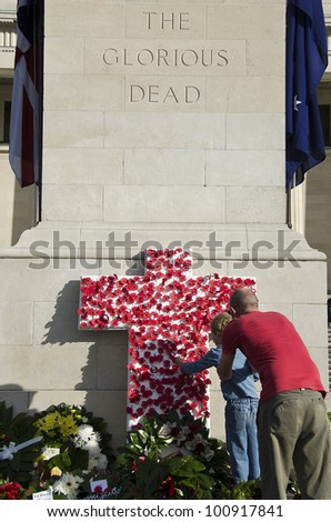 AUCKLAND, NEW ZEALAND - APRIL 25: A father and son place symbolic poppies on a cross at Auckland War Memorial Museum, following an Anzac Day service on April 25, 2012 in Auckland, New Zealand. - stock photo