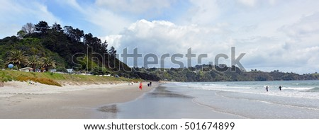 Auckland, New Zealand - October 04, 2016: Onetangi Beach panorama on Waiheke Island with people and waves in Spring.