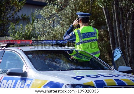 AUCKLAND,NZ - JUNE 03 2014:Traffic Police officer pointing his radar gun at speeding traffic.Traffic Police Monitor traffic to ensure motorists observe traffic regulations and safe driving procedures. - stock photo