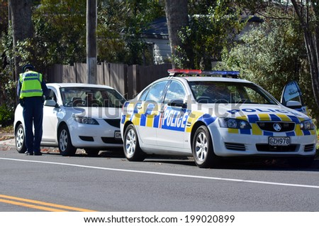 AUCKLAND,NZ - JUNE 03 2014:Traffic Police officer writing a traffic citation.Traffic Police Monitor traffic to ensure motorists observe traffic regulations and exhibit safe driving procedures. - stock photo