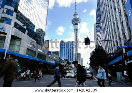 AUCKLAND, NZ - MAY 29:Traffic on Queen street with the Skytower in the background on May 29 2013.It's a major commercial thoroughfare in the Auckland CBD, New Zealand's main population center. - stock photo
