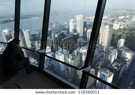 AUCKLAND, NZ - OCT 08: Visitors at the Sky Tower observation deck on Oct 08 2013.It's 328 metres (1,076ft) tall and it the tallest free-standing structure in the Southern Hemisphere. - stock photo