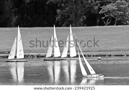 AUCKLAND, NZL - DEC 21 2014:Remote controlled sailing wooden yachts race in a pond.The racing is governed by the same Racing Rules of Sailing that are used for full-sized crewed sailing boats - stock photo