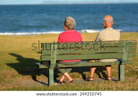 AUCKLAND, NZL - JAN 2015:Two old retired couple sit on a bench.By 2051, there will be over 1.14 million people aged 65 years and over in New Zealand. - stock photo