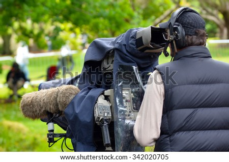 AUCKLAND,  NZL - NOV 22 2015: Camera operator shooting on location event. In 2006, there were approximately 27,000 television, video, and motion picture camera operators employed in the United States. - stock photo
