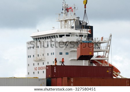 AUCKLAND,  NZL -OCT 13 2015:Cargo ship workers unloading containers in Ports of Auckland New Zealand.Itâ??s New Zealand's busiest port and the third largest container terminal in Australasia. - stock photo