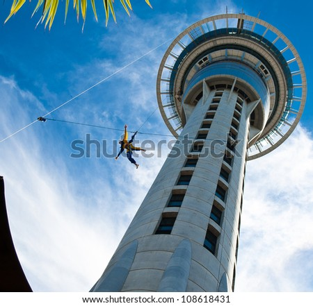 Auckland Sky Tower from below with blue sky and someone jumping off - stock photo
