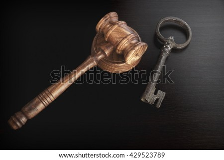 Auctioneers or Judges Hammer or Gavel with Old Key On Black Wooden Background, Trial Or Auction Concept - stock photo