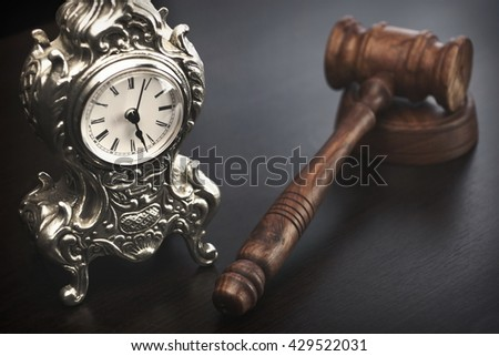 Auctioneers or Judges Hammer or Gavel with Old Silver Clock On Black Wooden Background, Time For Trial Concept - stock photo
