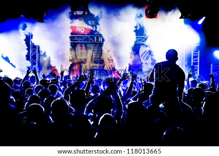 Audience Crowd Man on Shoulders Silhouette Dancing to DJ Pete Tong at Cream Nightclub Party. Nightlife Lazer Show Hands In Air With Smoke Cannon Blast - stock photo