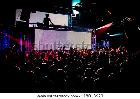Audience Crowd Silhouette Dancing to DJ Pete Tong at Cream Nightclub Party. Nightlife Lazer Show Hands In Air - stock photo